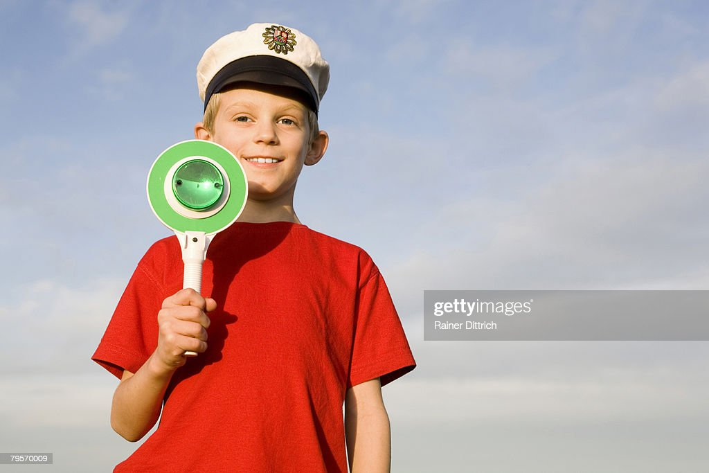 'Boy (10-12) wearing police cap, holding green sign' : Stock Photo