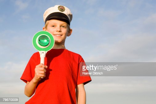 'Boy (10-12) wearing police cap, holding green sign' : Photo