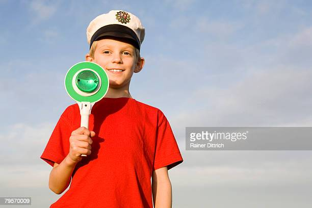 'Boy (10-12) wearing police cap, holding green sign'
