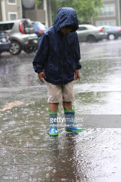 Boy Wearing Raincoat Standing On City Street During Rainy Season