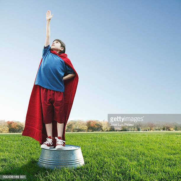 Boy (8-10) wearing red cape standing on washtub (Digital composite)
