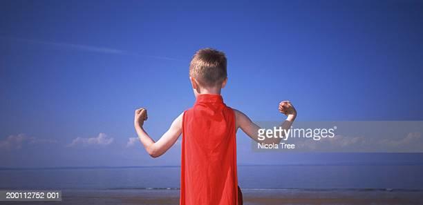 Boy (5-7) wearing red superhero cape flexing muscles, rear view