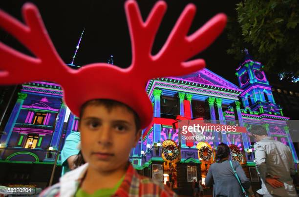 A boy wearing reindeer antlers looks on as Melbourne Town Hall is illuminated with Christmas projections as Melbourne lights up for Christmas on...