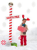 Boy (4-5) wearing reindeer antlers standing next to North Pole sign