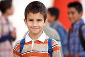 Boy (8-10) wearing rucksack, smiling, portrait, close-up