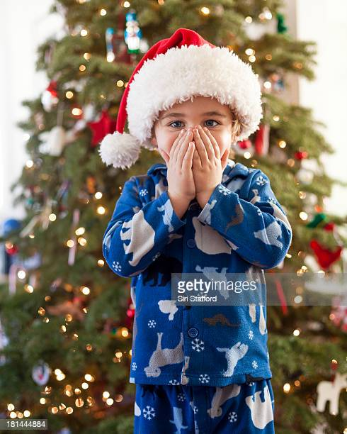 Boy wearing Santa hat with hands over his mouth