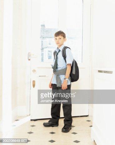 Boy (8-10) wearing school uniform and rucksack, standing by front door : Stock Photo