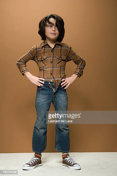 Boy (8-9) wearing short jeans, hand on hips