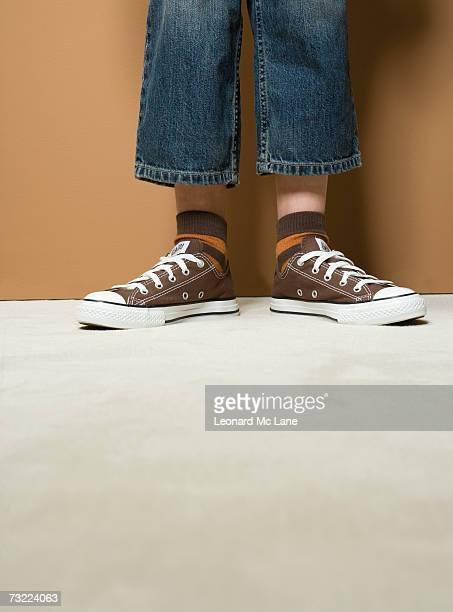 Boy (8-9) wearing short jeans, low section