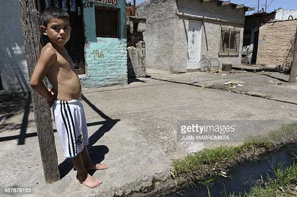 A boy wearing shorts of the Real Madrid football team stands by a ditch with sewage in the Villa Jardin shantytown near the Riachuelo stream in Lanus...