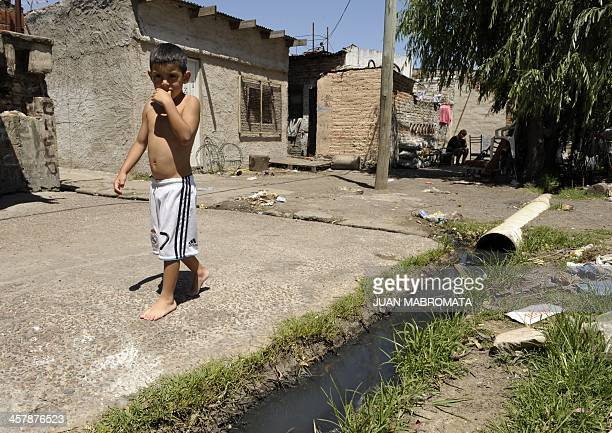 A boy wearing shorts of the Real Madrid football team walks beside a ditch with sewage in the Villa Jardin shantytown near the Riachuelo stream in...