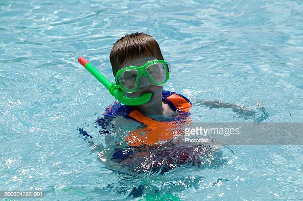 Boy (8-9), wearing snorkel and mask in swimming pool, portrait