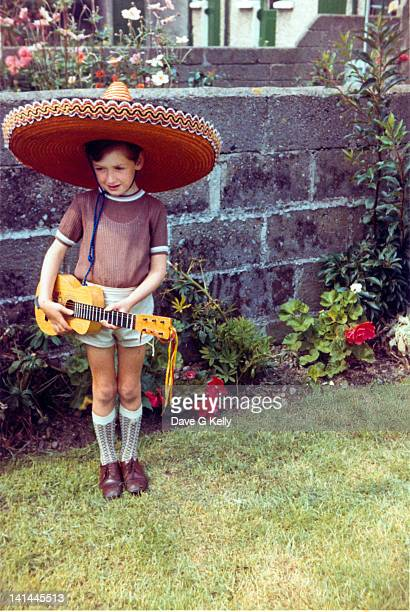Boy wearing sombrero strumming