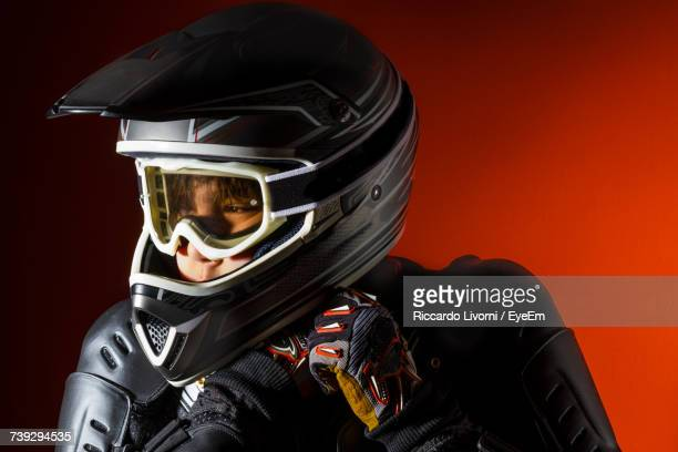 Boy Wearing Sports Helmet Against Red Background