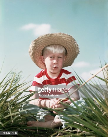 Boy wearing strawhat holding fishing pole stock photo for Fishing straw hat