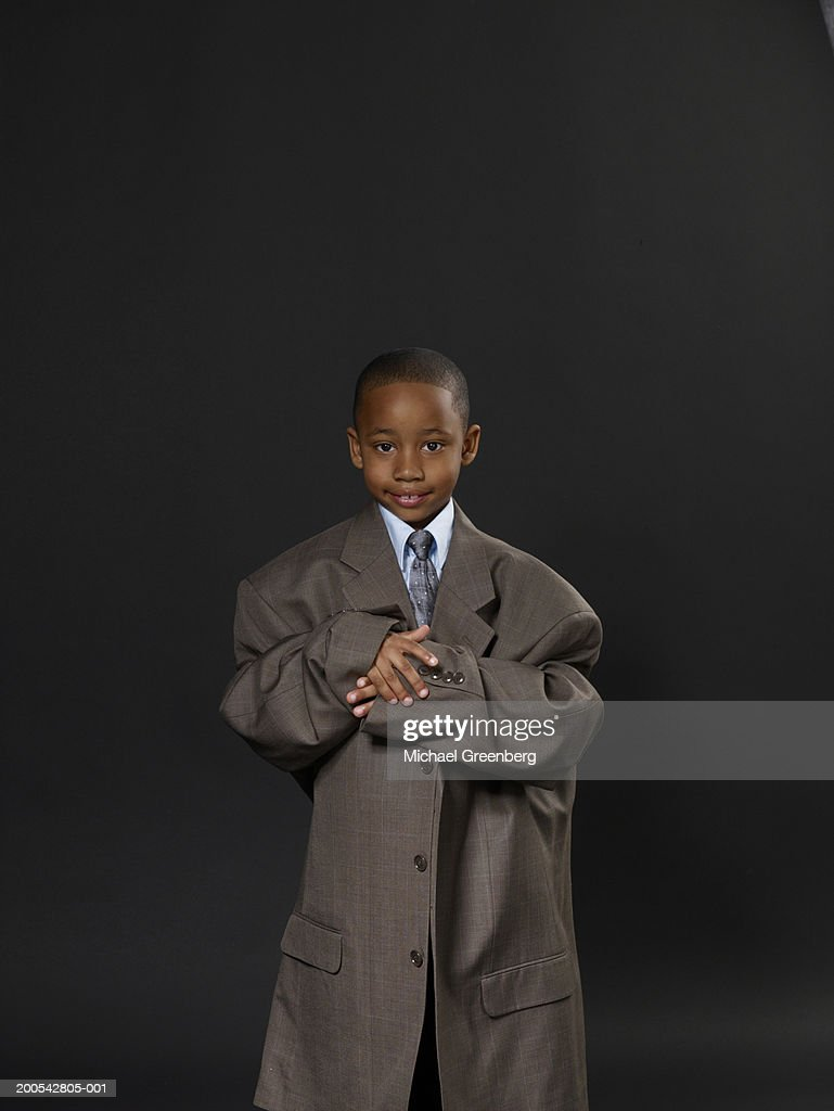 Boy (5-7) wearing suit and oversize topcoat, portrasit : Stock Photo