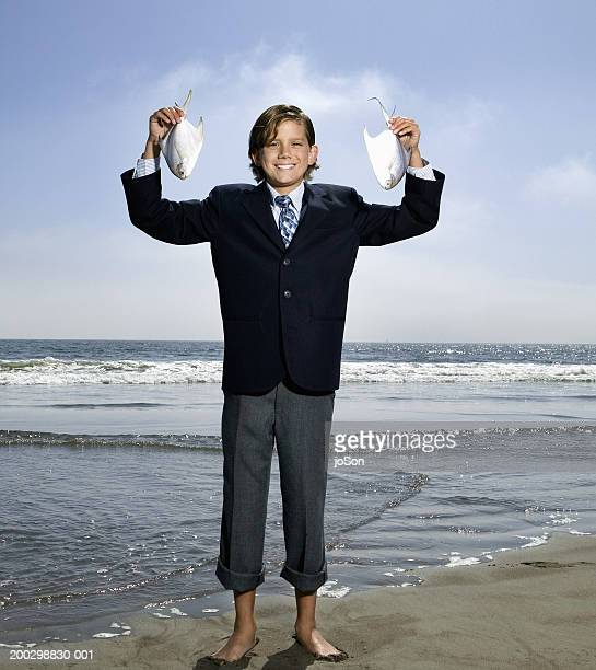 Boy (12-14) wearing suit, holding fish at beach, portrait, summer