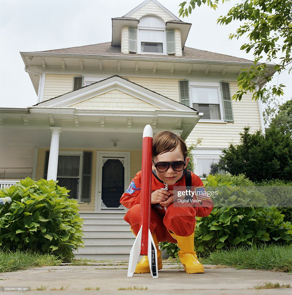 Boy (3-5) wearing sunglasses, crouching by toy rocket