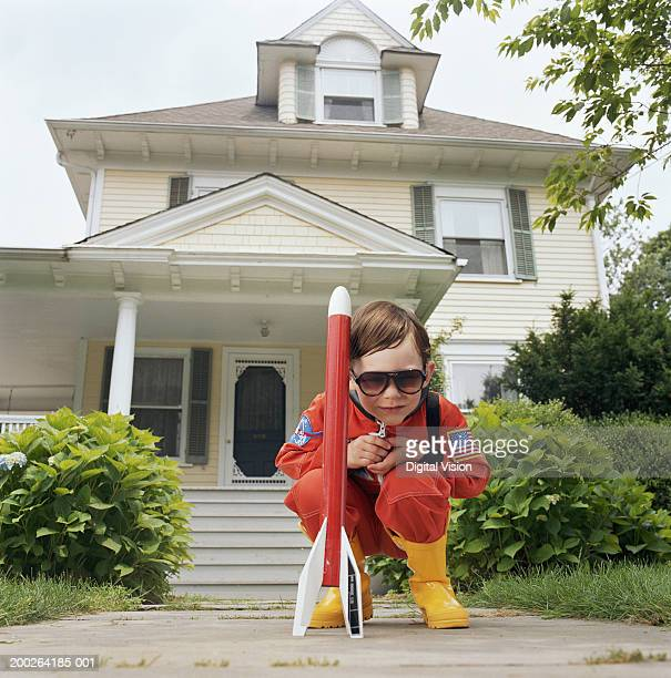 Boy (3-5) wearing sunglasses, crouching by toy rocket