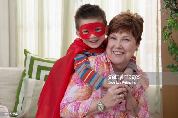 Boy wearing superhero costume hugging grandmother