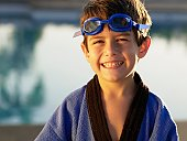 Boy wearing swimming goggles and gown (portrait)