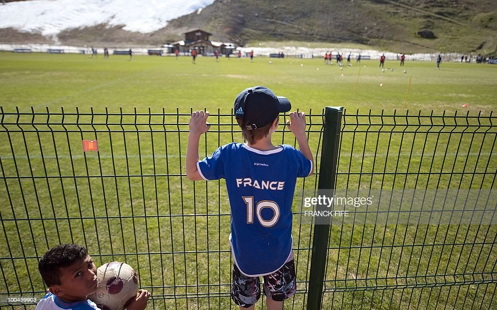 A boy (C) wearing the French national football team jersey watches the French squad during a training session, on May 24, 2010, near Tignes in the French Alps, as part of the preparation for the upcoming World Cup 2010. France will play against Uruguay in Capetown in its group A opener match on June 11.