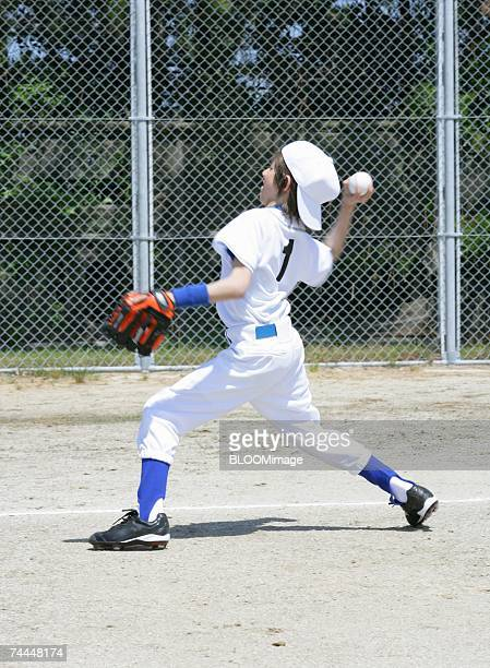Boy wearing uniform of baseball throwing ball in ground