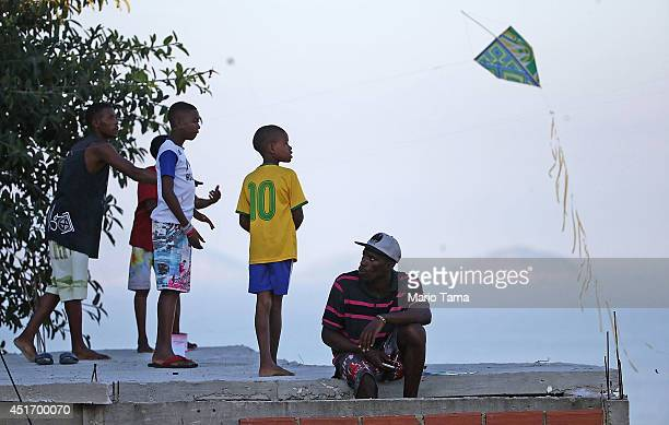 A boy wears a Neymar jersey as Brazilians fly kites from a rooftop in the Cantagalo favela before the BrazilColombia match on July 4 2014 in Rio de...