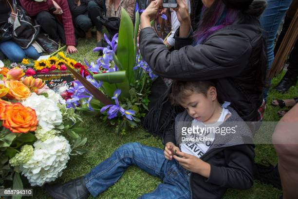 A boy wears a shirt referencing the song Say Hello to Heaven as fans mourn graveside after funeral services for Soundgarden frontman Chris Cornell at...