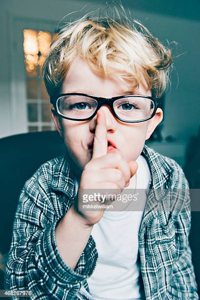 Boy wears glasses and makes a sign to be quiet