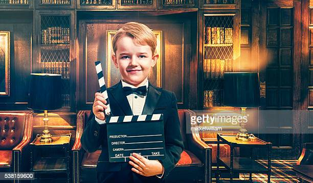 Boy wears tuxedo and holds film slate on location