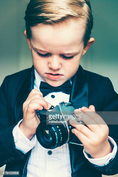 Boy wears tuxedo and plays with old retro camera