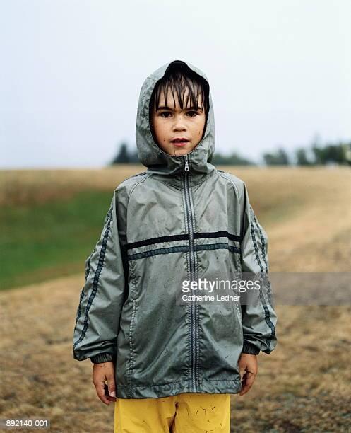 Boy (7-9) wet from rain, wearing hooded jacket