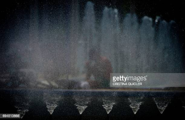 TOPSHOT A boy wets himself with water from a street fountain in Sevilla on June 10 2017 QUICLER