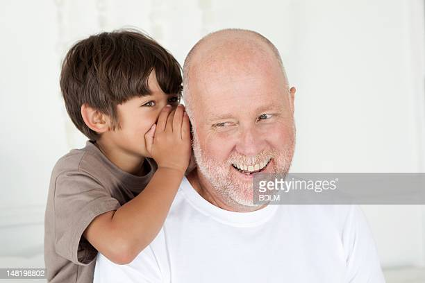 Boy whispering in fathers ear