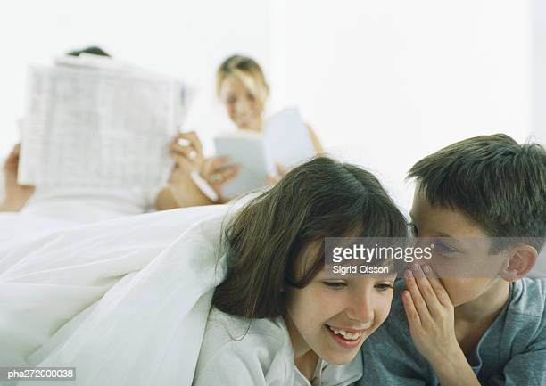 Boy whispering to girl, parents reading in background