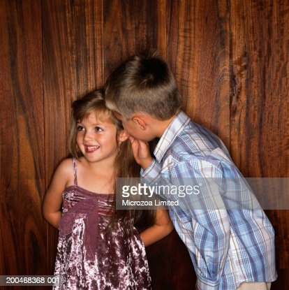 Boy (3-5) whispering to girl (2-4), smiling : Stock Photo