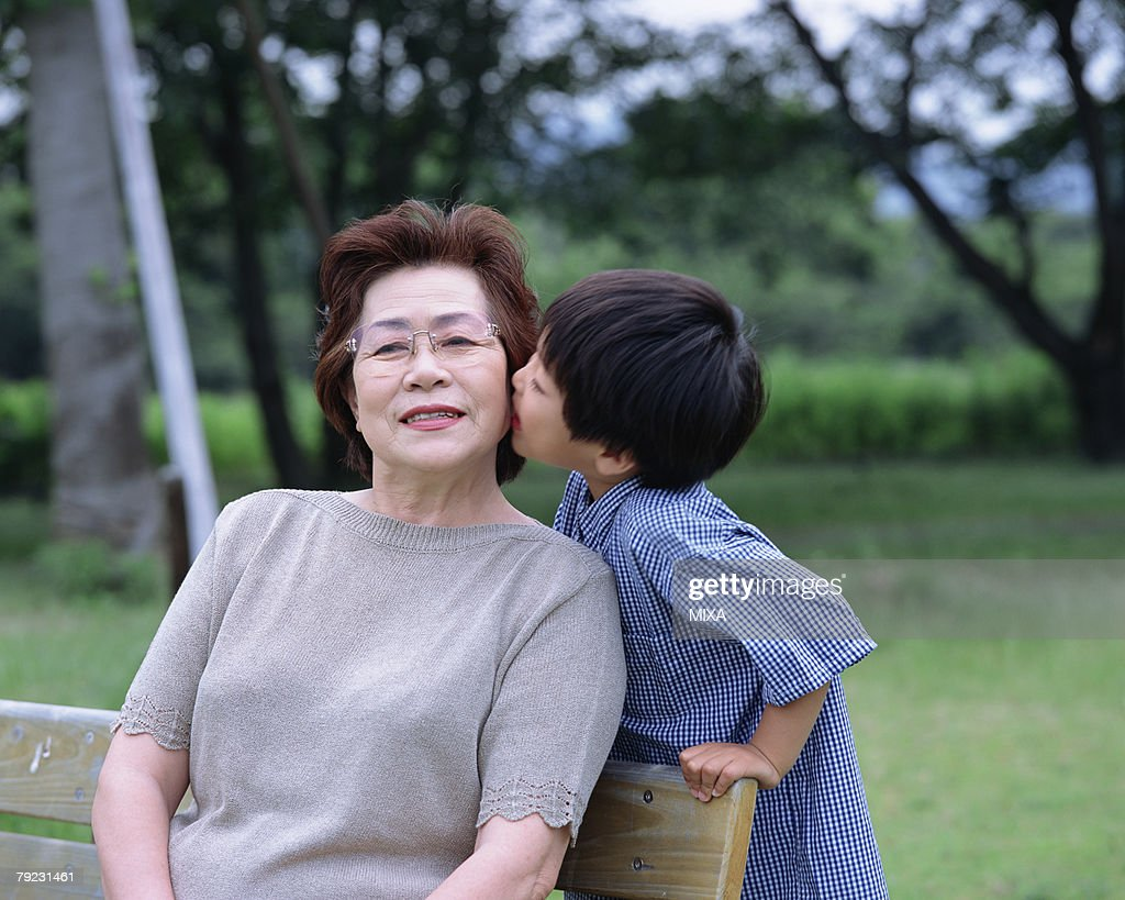 A boy whispering to grand mother : Stock Photo