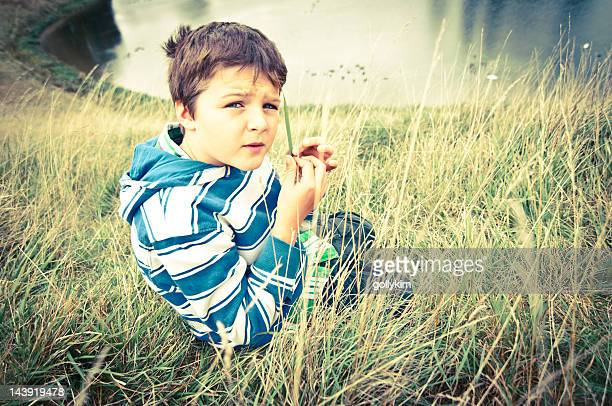 Boy whistles with a blade of grass