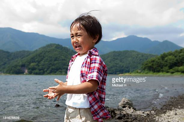 Boy who is falling over and crying by the lake