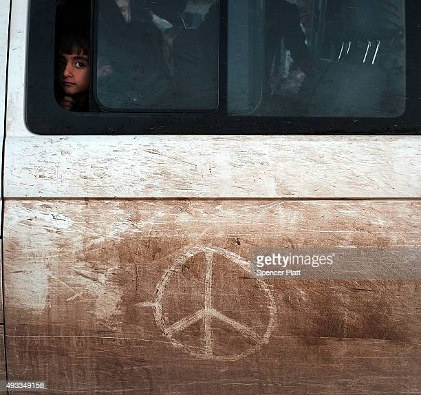 A boy who just arrived from Turkey looks out of a bus window at a refugee reception center on the island of Lesbos on October 19 2015 in Sikaminias...