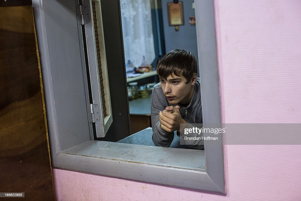 A boy who lives at a facility for at-risk teenage boys run by City Without Drugs takes a break from cooking dinner on October 16, 2013 in Yekaterinburg, Russia. Nine boys, many of whom were either experimenting with drugs or had dropped out of school, live at the group home, where school attendance and homework are mandatory. City Without Drugs is a well-known narcotics treatment program in Russia founded by Yevgeny Roizman, who was elected mayor of Yekaterinburg in September 2013.