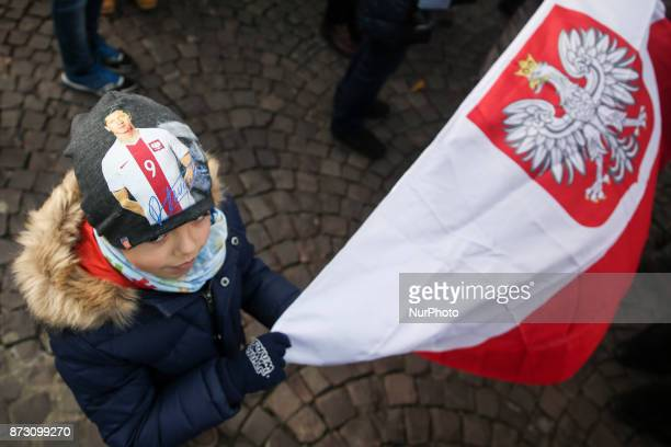 A boy who wears a beanie with Robert Lewandowski's picture holds a Polish flag during the official celebration of the Polish Independence Day Krakow...