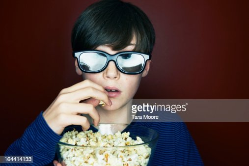 boy with 3d glasses and popcorn looking amazed : Stock Photo
