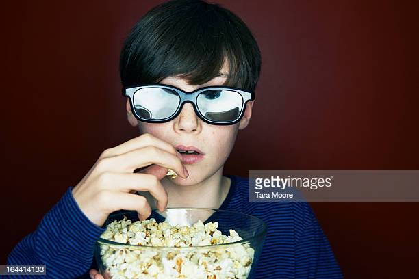 boy with 3d glasses and popcorn looking amazed