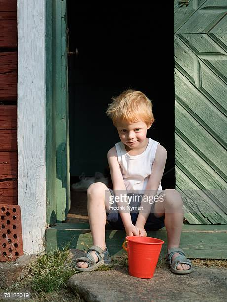 A boy with a bucket sitting in the doorway.