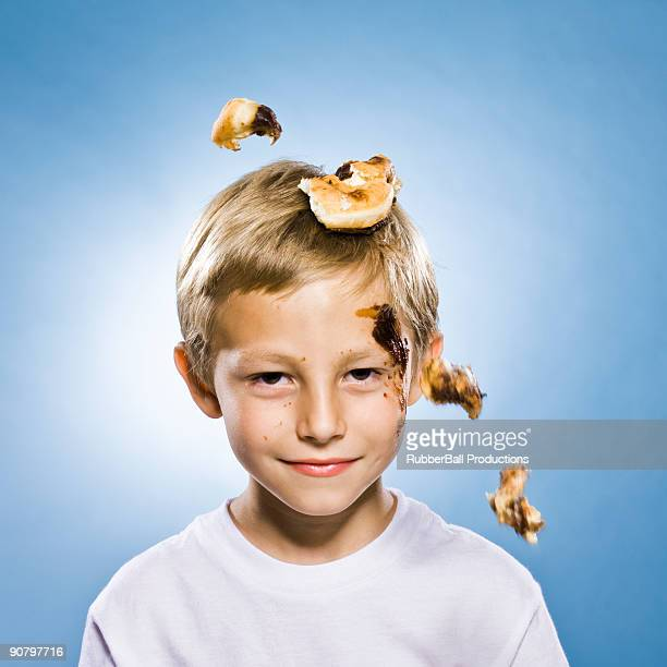 boy with a chocolate doughnut falling on his head