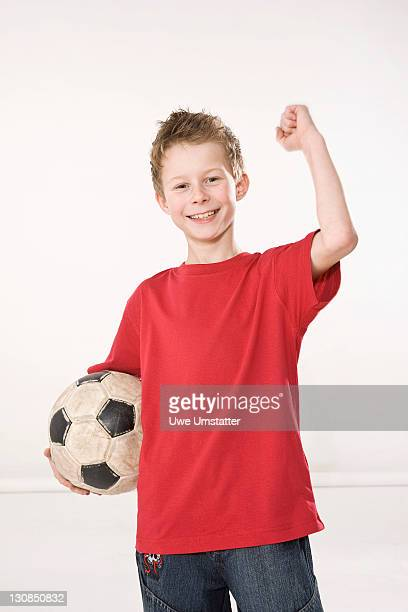 Boy with a football under his arm striking a victory pose