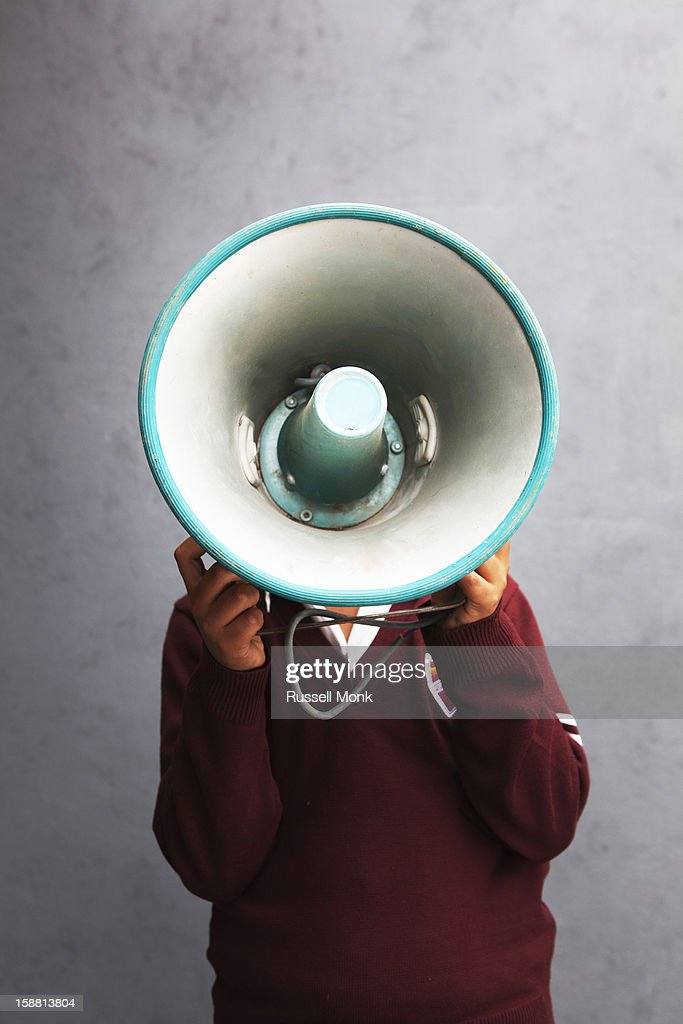 Boy with a speaker in front of his face : Stock Photo