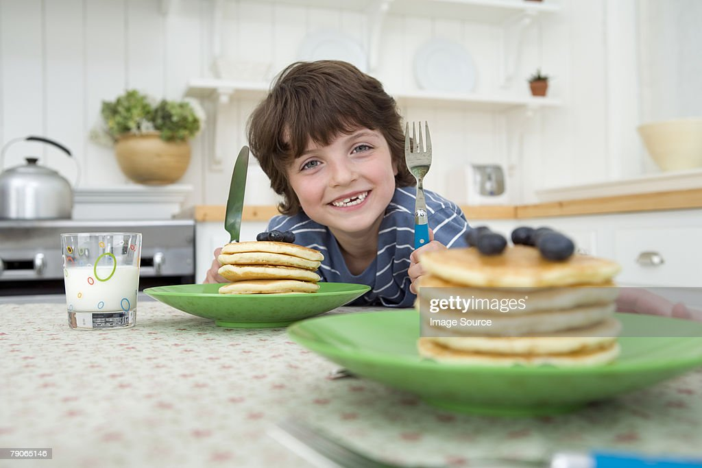 Boy with a stack of pancakes : Stock Photo